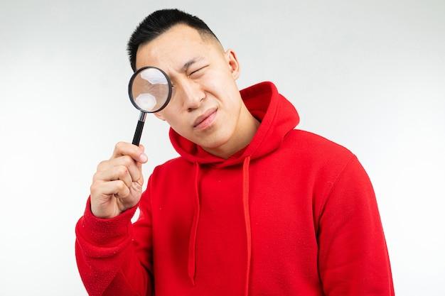 Brunette mann in einem roten pullover, der die kamera durch eine lupe auf einem weißen isolierten hintergrund betrachtet.