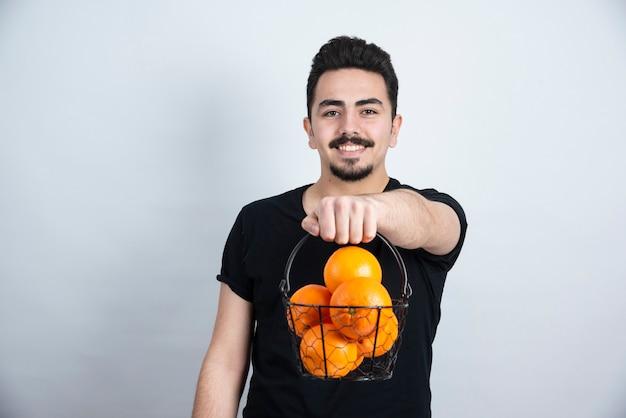 Brunette mann modell stehend und hält metallkorb mit orangenfrüchten.
