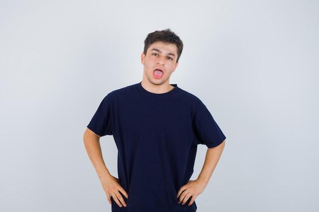 Brunette mann öffnet mund, posiert mit den händen auf taille im t-shirt und schaut konzentriert, vorderansicht.