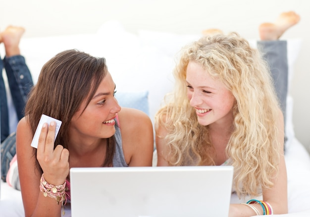 Brunette und blonde mädchen, die online in einem schlafzimmer kaufen