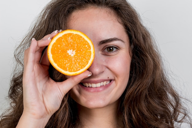Brunettefrau, die eine orange anhält