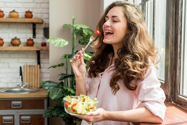Brunettefrau, die einen salat isst