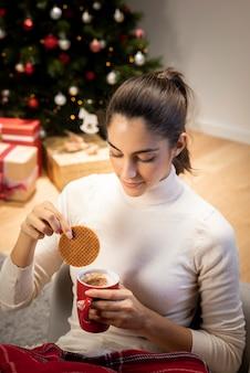 Brunettefrau, die einen tasse kaffee betrachtet