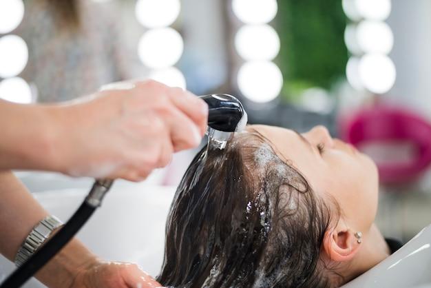 Brunettefrau, die ihr haar gewaschen erhält