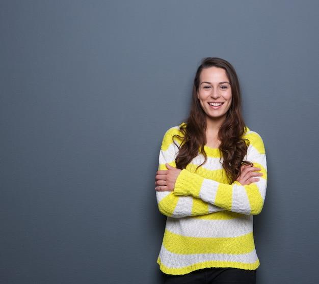 Brunettefrau, die mit den armen gekreuzt lächelt