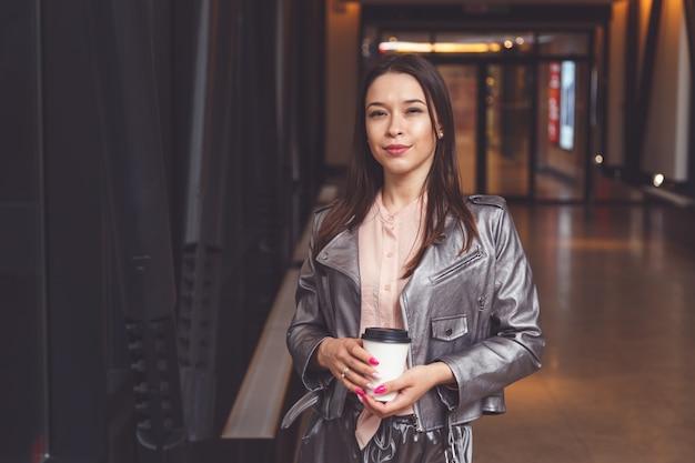 Brunettefrau, die mitnehmerkaffee hält