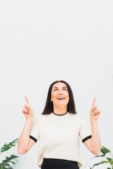 Brunettefrau, die oben finger zeigt