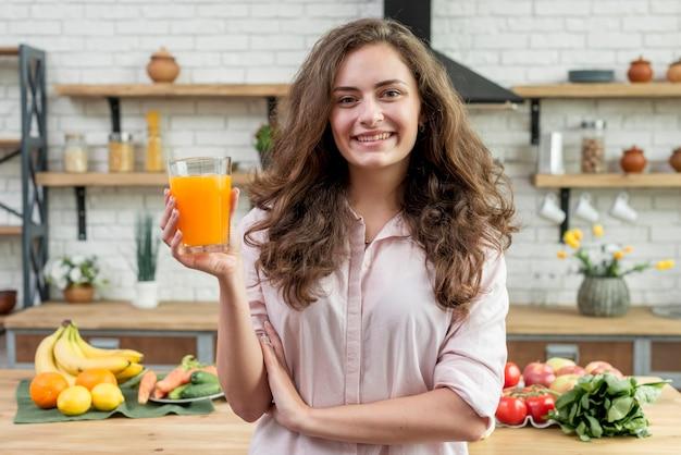 Brunettefrau, die orangensaft trinkt