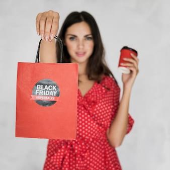 Brunettefrau, die schwarze freitag-einkaufstasche hält