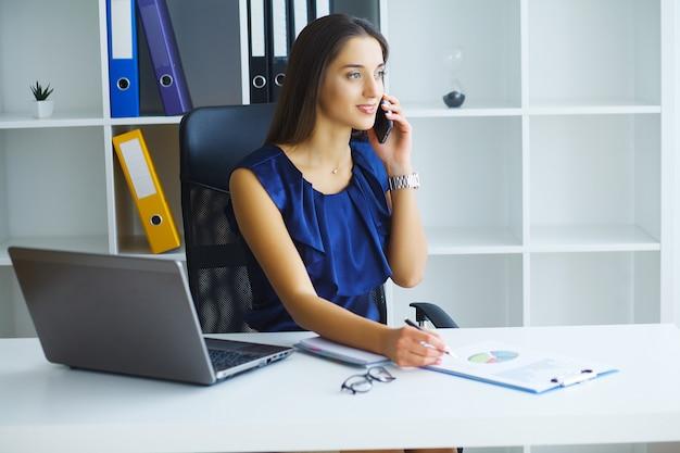 Brunettefrau, die telefon beim arbeiten betrachtet