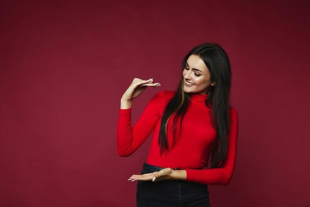 Brunettefrau hat glücklichen blick und zeigt etwas, das auf einer rotweinfarbe steht