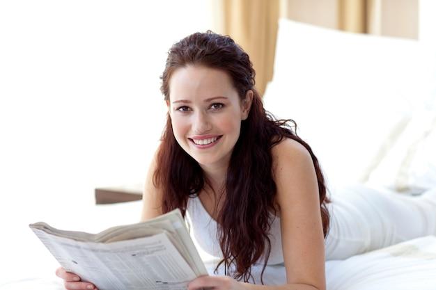 Brunettefrau im bett eine zeitung und ein lächeln lesend