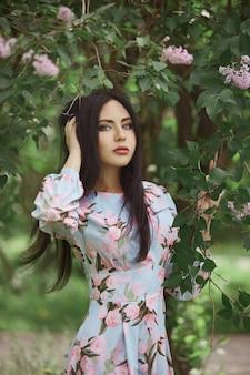 Brunettefrau in den niederlassungen eines schönen blühenden baums. kurzes sommerkleid