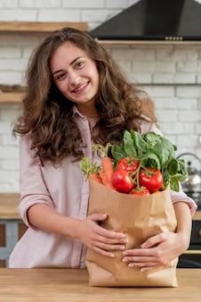 Brunettefrau mit einer papiertüte voll vom gesunden lebensmittel