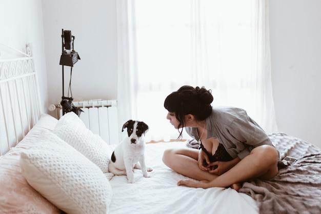 Brunettefrau mit ihrem süßen welpen im schlafzimmer