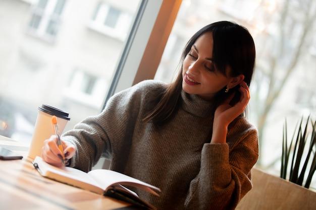 Brunettefrau mit notizbuch arbeitet in einem café