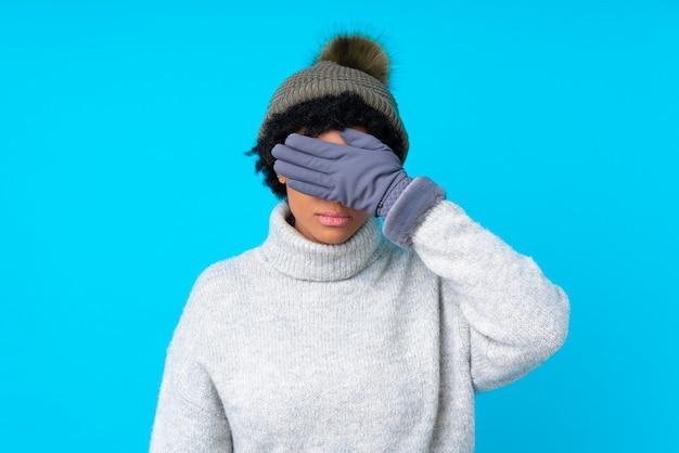 Brunettefrau mit winterhut über getrenntem blauem hintergrund