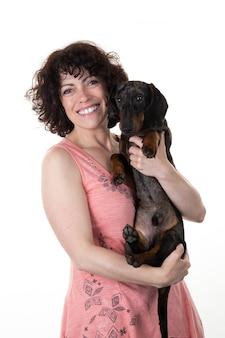 Brunettefrau und zarte umarmungen eines hundes lokalisiert auf weiß