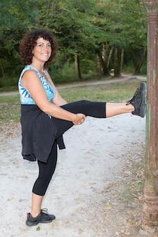 Brunettefrauenmitte alterte das ausdehnen von beinen in einem park