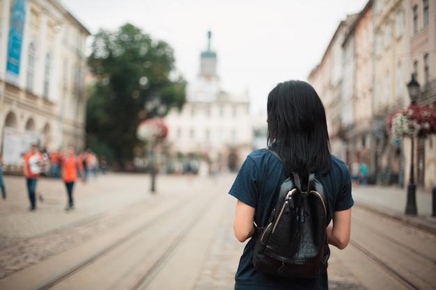 Brunettefrauentourist mit einem ledernen rucksack, der in eine alte stadt lviv geht. platz für text
