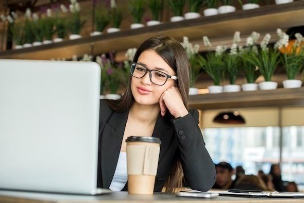 Brunettegeschäftsfrau, die den laptop verwendet