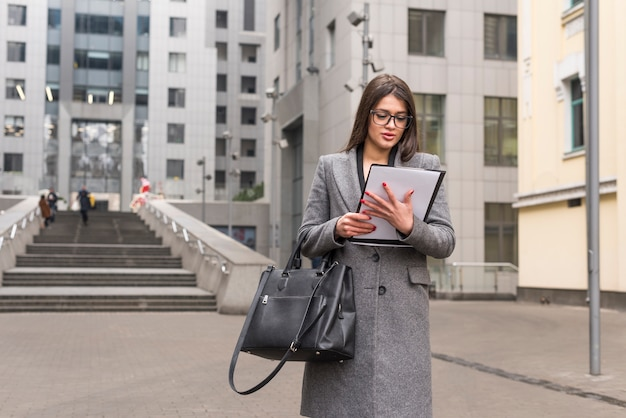 Brunettegeschäftsfrau, die draußen dokument liest