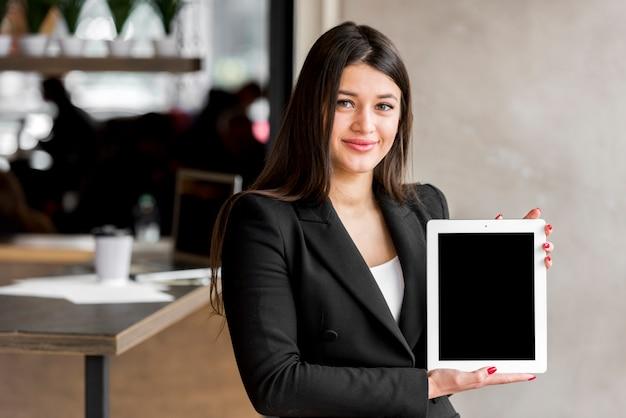 Brunettegeschäftsfrau, die eine tablette zeigt