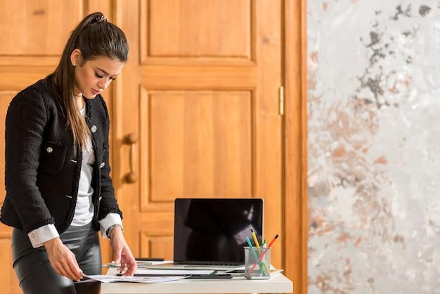 Brunettegeschäftsfrau, die ihre papiere organisiert