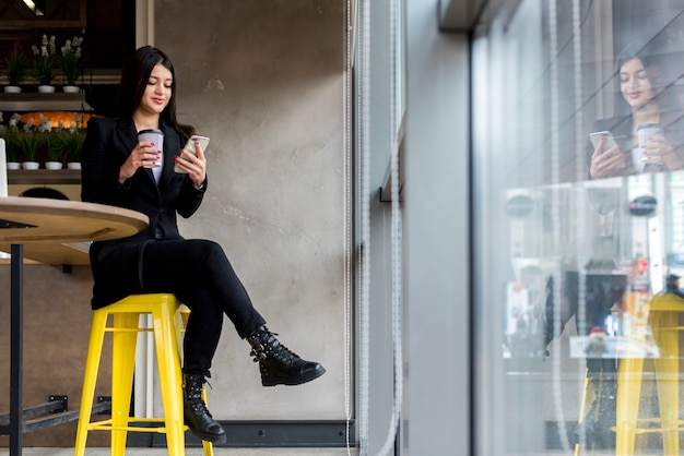 Brunettegeschäftsfrau, die ihren smartphone verwendet
