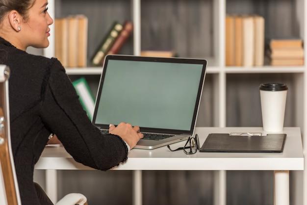 Brunettegeschäftsfrau, die in ihrem büro arbeitet