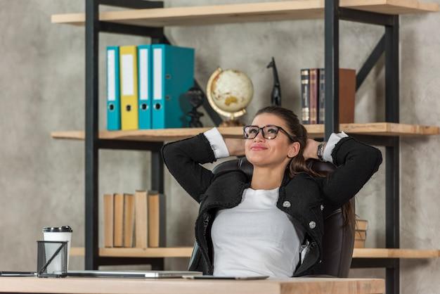 Brunettegeschäftsfrau, die in ihrem büro sich entspannt