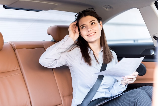 Brunettegeschäftsfrau, die innerhalb eines autos aufwirft