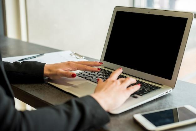 Brunettegeschäftsfrau, die laptop verwendet