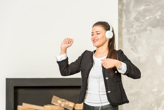 Brunettegeschäftsfrau, die musik hört
