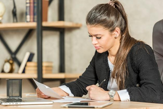 Brunettegeschäftsfraulesung in ihrem büro