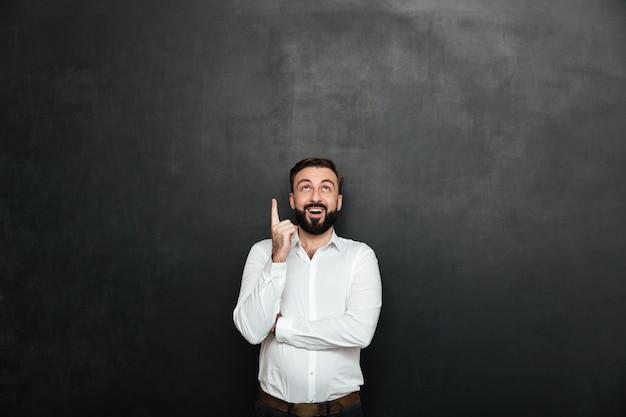 Brunettegeschäftsmann in der formellen kleidung, die auf kamera mit dem breiten lächeln, annoncierend mit dem zeigefinger oben über dunkelgrauem kopienraum aufwirft
