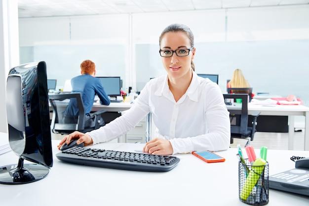 Brunetteglasgeschäftsfrau, die im büro arbeitet