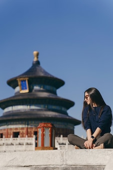 Brunettemädchen, das auf den schritten durch tempel von heven in china sitzt