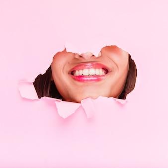 Brunettemädchen, das durch ein papierloch aufwirft