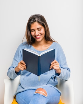 Brunettemädchen, das ein buch lesend sitzt