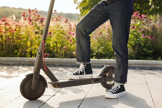 Brunettemädchen, das einen umweltfreundlichen elektrischen trittroller in einem park im sonnigen wetter auf bürgersteigen reitet