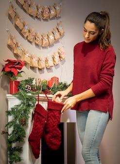 Brunettemädchen, das geschenk in weihnachtsstrumpf einsetzt