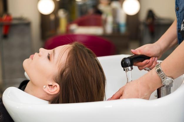 Brunettemädchen, das ihr haar gewaschen erhält