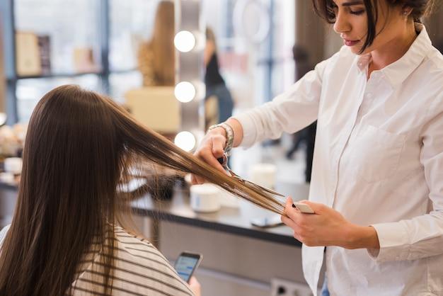 Brunettemädchen, das ihren haarschnitt erhält