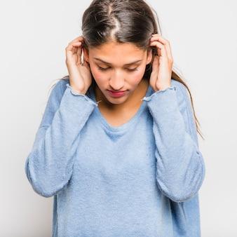 Brunettemädchen, das mit blauer strickjacke aufwirft