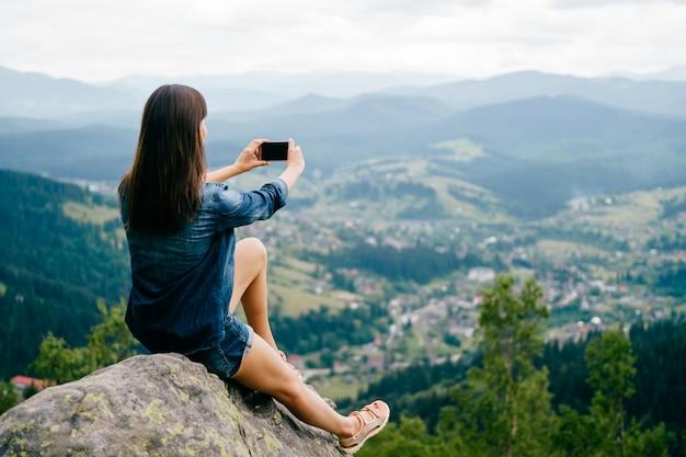 Brunettemädchen, das selfie mit dem smartphone hoch in den bergen nimmt.
