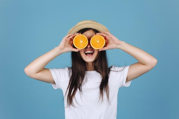 Brunettemädchen im gelben rock hält orangen vor ihren augen und lächelt