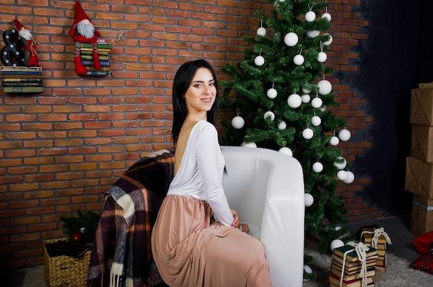 Brunettemädchen im kleid warf nahe baum des neuen jahres mit weihnachtsdekoration im ziegelsteinstudioraum auf.