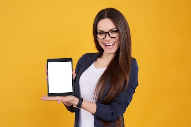 Brunettemädchen in den gläsern wirft mit weißer tablette auf