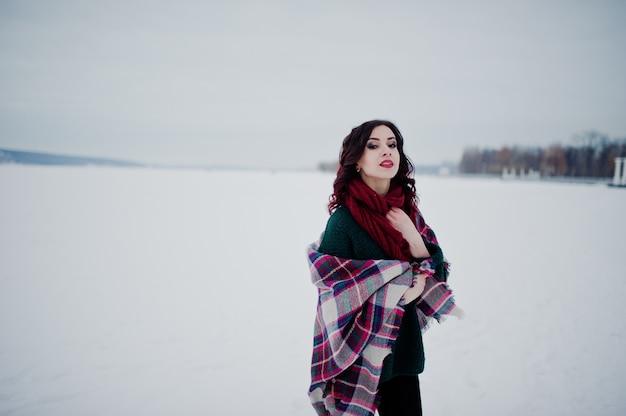 Brunettemädchen in der grünen strickjacke und im roten schal mit gefrorenem see des plaids im freien am abendwintertag.